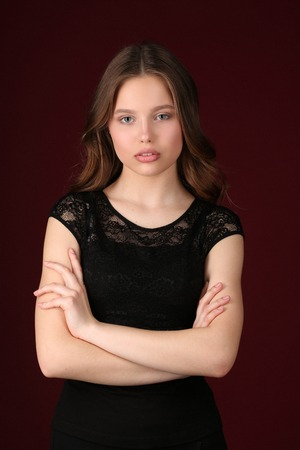 collarbone: Girl with crossed arms, girl in black dress, high fashion look, beautiful girl, smiling girl, isolated, long hair, perfect make-up, big lips, model in studio, close up, dark red background