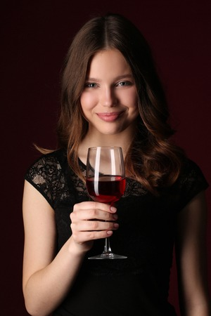 bocal: Standing girl with bocal, girl with wineglass, high fashion look, beautiful girl, brunette girl, isolated, model in studio, long hair, close up, dark red background