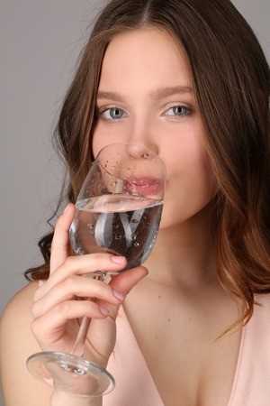 bocal: Lady drinking water from a bocal, high fashion look, healthy lifestyle, beautiful girl, smiling girl, isolated, perfect make-up, big lips, model in studio, close up, gray background