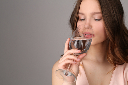 vasos de agua: Teen drinking water from a bocal, high fashion look, healthy lifestyle, beautiful girl, smiling girl, isolated, perfect make-up, big lips, model in studio, close up, gray background