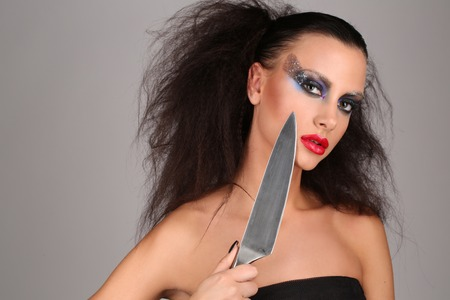 Girl with knife, wild girl, high fashion look, perfect make-up, isolated, red lips, dark and mysterious, serious girl, model in studio, close up, gray background