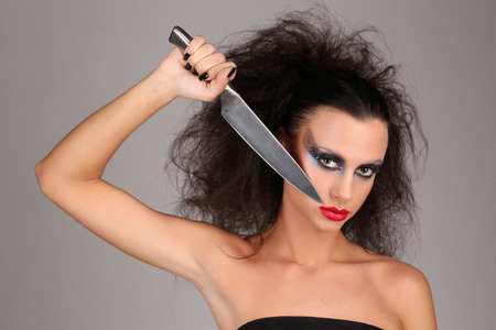 Girl with knifeand wild hair, high fashion look, perfect make-up, isolated, red lips, dark and mysterious, serious girl, model in studio, close up, gray background