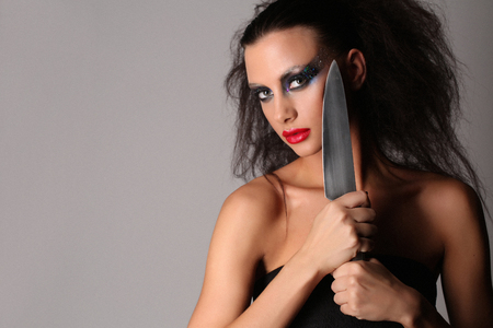 Model with knifeand wild hair, high fashion look, perfect make-up, isolated, red lips, dark and mysterious, serious girl, model in studio, close up, gray background