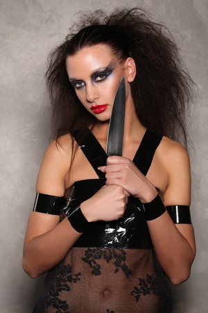 Dangerous woman with knifeand wild hair, high fashion look, perfect make-up, isolated, red lips, dark and mysterious, serious girl, model in studio, close up, gray background