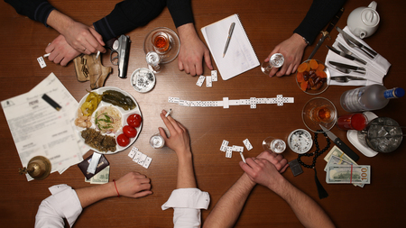 People playing domino, gambling, board games, intelligence match, smoking cigarettes, man with a gun, alcohol on the table, casino, close up Stock Photo