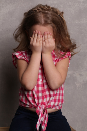 girl with gray eyes: Little girl closing her eyes with hands, happy childhood, little girl, happy family, fashion clothes, cute baby, beautiful girl, blonde girl, isolated, baby in studio, gray background Stock Photo
