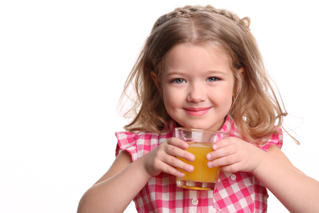 Babygirl with a glass of juice, happy childhood, little girl, happy family, fashion clothes, cute baby, blonde girl, isolated, baby in studio, white background Stock Photo