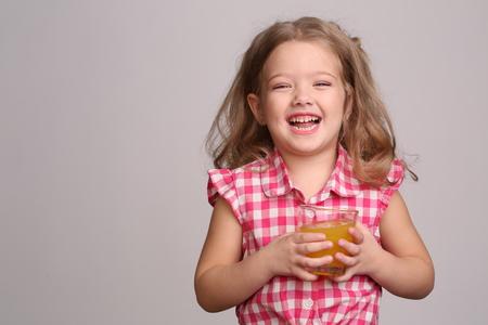 niños rubios: Niño posando con un vaso de naranja fresca, feliz niñez, niña, familia feliz, ropa de moda, lindo bebé, chica rubia, aislado, bebé en estudio, fondo gris