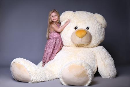子供の大きなクマのぬいぐるみ、ぬいぐるみ、ぬいぐるみ、大きなぬいぐるみ、子供とギフト、薄紫色のドレス、ブロンドの女の子、スタジオでは 写真素材