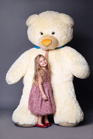 Little girl in dress standing near the large teddy bear, stuffed animals, plush animals, big plush toys, kids and gifts, lilac dress, blonde girl, baby in studio, Stock Photo