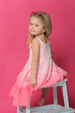 empty room background: Little model sitting back on chair, old furniture, kid clothing, cute baby, blonde girl, baby in studio, close up, pink background Stock Photo