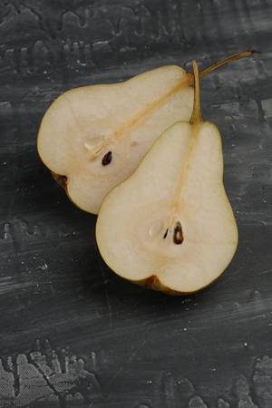 two and a half: Two pears cut in half on the table, food for restaurant, ingredients and preparation, fruits and vegetables, close up