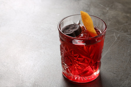 sweet vermouth: Negroni in a glass beaker with a slice of orange. Close up Stock Photo