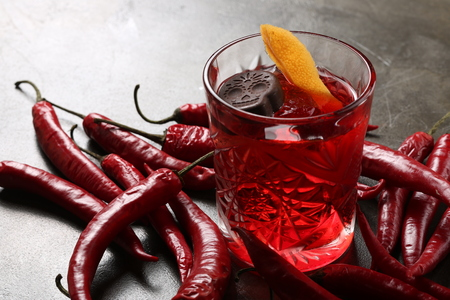 Negroni and red hot peppers on the table. Close up