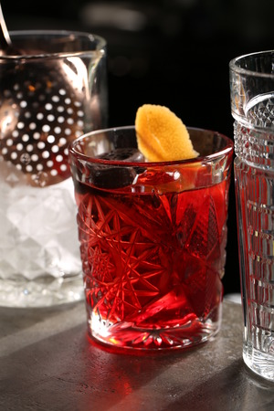 Glass of Negroni between two drinks. Close up