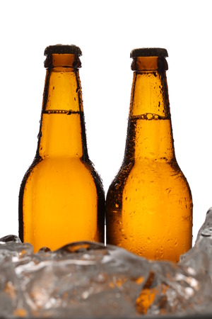 Two bottles of cider in ice cubes. Close up. White background Stock Photo