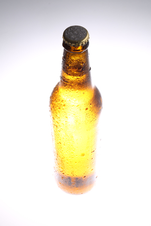 Standing bottle of fresh beer. Close up. White background