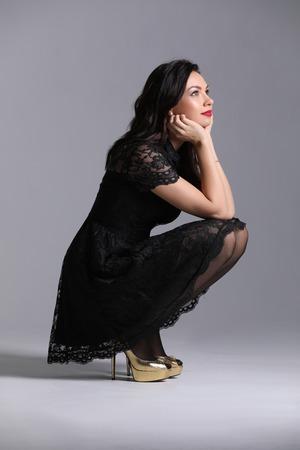 Girl squatting. Gray background. Photographie retouchee Foto de archivo