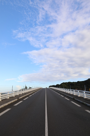 Straight and smooth asphalt road with one continuous marking. Blue sky background