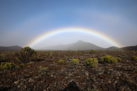 Over a few mountains in the fog stretched a rainbow