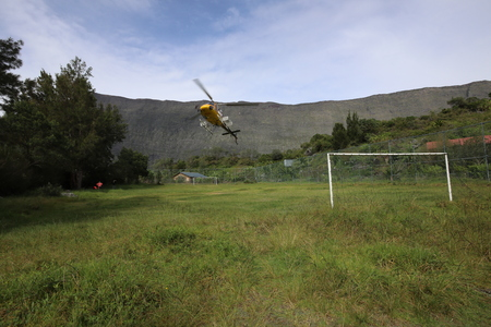 Football field in the mountains where a helicopter lands Stock Photo