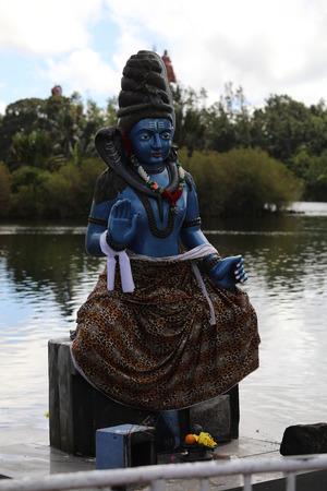 Blue statue of Shiva stands near the seashore 写真素材