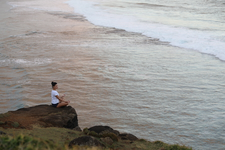 Girl posing sitting on a stone cliff