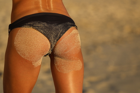 Primo piano ragazza bottino in costume da bagno e nella sabbia