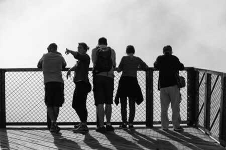 Reunion may 5, 2018: Black and white photo five people stand on the bridge behind which there is heavy fog Redactioneel