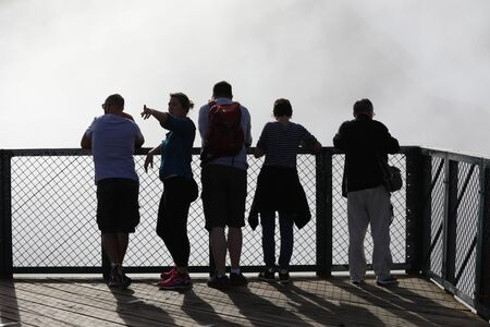 Reunion may 5, 2018: Five people stand on the bridge behind which there is heavy fog