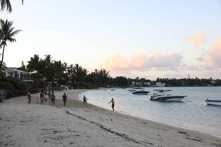 Reunion may 5, 2018: Sunset on the beach of the island of Mauritius, where yachts float on the water and people play on the beach