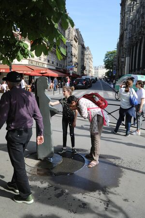PARIS may 5, 2018: People in the street in the heat wash their face from a fountain