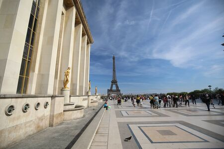 PARIS may 5, 2018: Tourists walk around the building with golden women and the Eiffel Tower is clearly visible Redactioneel