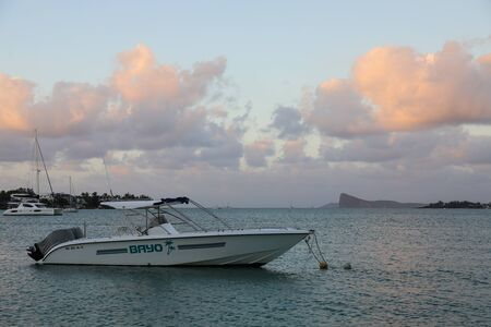 Reunion may 5, 2018: Sunset on the beach of the island of Mauritius where yachts float on water Redactioneel