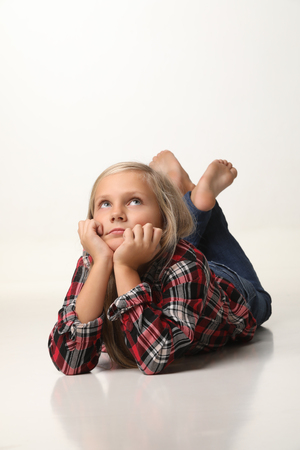 Girl with long blond hair is lying thoughtfully on the floor. White background