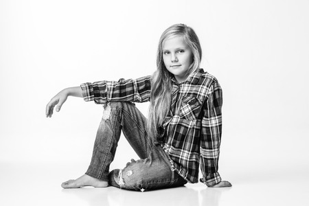 Photo black and white girl with long blond hair sits on the floor. White background