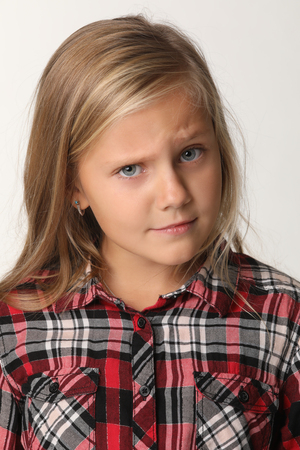 Close up of a portrait of a girl with blue eyes and blond hair. White background Banco de Imagens
