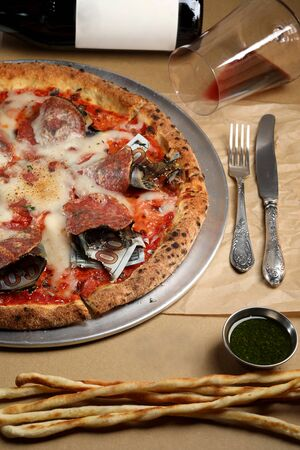 original pizza stuffed with dollars, served in a restaurant table, top view