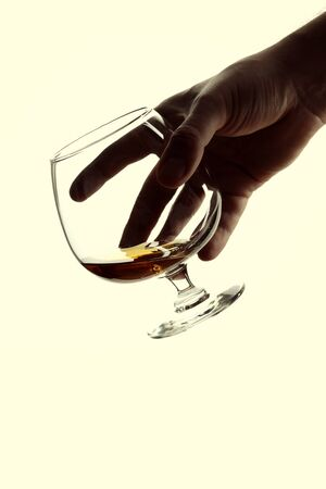 Male hand holding a glass of brandy isolated on white background.
