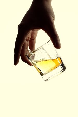Male hand holding a glass of whiskey with ice cubes. Isolated on white background 版權商用圖片