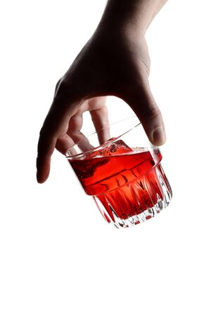 Male hand holding a glass of negroni cocktail with ice cubes.