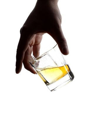 Male hand holding a glass of whiskey with ice cubes.