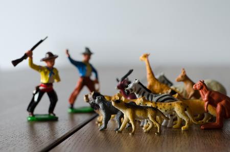 Hunters against wild animals. Miniature plastic figures. Soft focus effect.