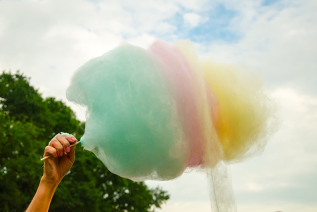 The hand of women holding coloured  cotton candy in the background of the blu