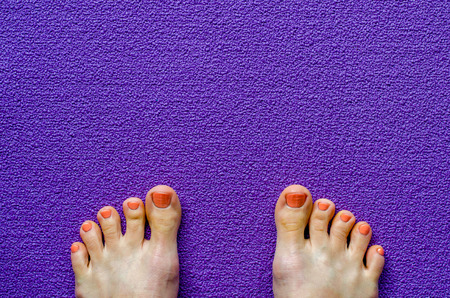 Womans foot on yoga mat. Top view