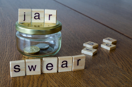 Swear jar on the wooden table background. Letters on wooden blocks.