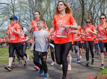 Mother in orange t-shirts with her son marathon in the park in spring. Wroclaw, Poland - April 7, 2019