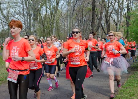 Huge group of women in orange t-shirts with numbers. Marathon in the park in spring. Wroclaw, Poland - April 7, 2019.