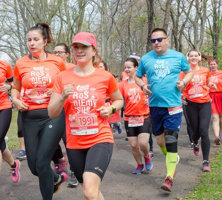 Huge group of women in orange t-shirts with marathon in the park in spring. Wroclaw, 新聞圖片