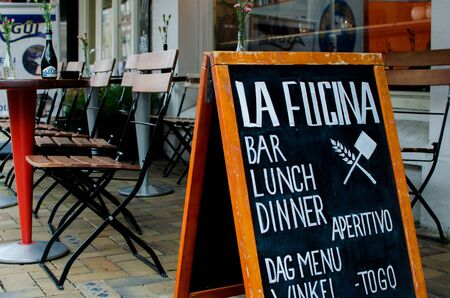 Pizza restaurant La fucina, Javastraat street, Amsterdam, Netherlands. View of advertising board. Table and chairs.